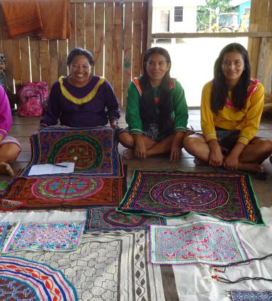 five women sit with their weaving laid out in front of them
